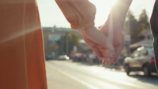 Young romantic couple holds their hands in the city center on a bright sunlight. Happiness, romantic atmosphere, dating. Togetherness, romance. Love story