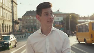 Young smiling man in elegant white shirt walks down the busy city street, actively using his smartphone. Modern technologies, chatting, being online, social networks. Male portrait