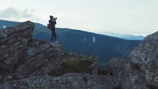 Young stylish female photographer with backpack stands on the high rocky ledge holds the camera and overlooks the green mountain hills, takes the photo. Stunning nature scenery.