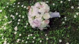 Wedding bouquet of pink roses and peonies lying on the green grass, surrounded by chamomiles. No people around. Outside shooting, green grass on the background. Wedding atmosphere.