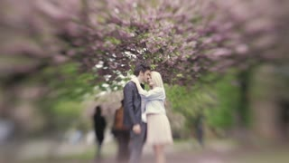 Young blonde girl touching her boyfriend kisses him in the nose, then looks away. City in spring. Portrait. Spring time. Outside shooting, people on the background. Atmosphere of love.