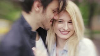 Young European couple hugging and kissing each other. Forever in love. Love is in the air. Portrait, outside shooting, windy weather. Lensbaby, close up view, slow motion.