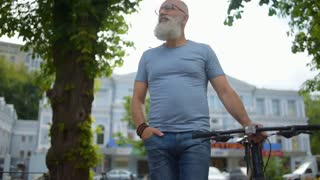 Amazed greyhaired man with bicycle examining city during walk