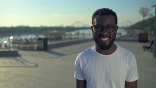 Beaming African American guy moving toward camera