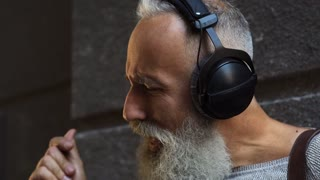Bearded man with headphones singing outdoors