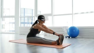 Body training. Full length of attractive young woman doing stretching exercises while sitting on the floor and looking through virtual glasses