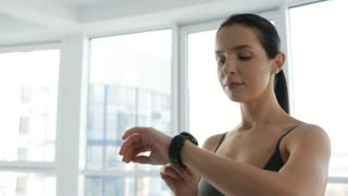 Caring about health. Close up of young cheerful woman measuring her heart rate while looking the sport watch and being concentrated