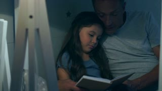 Caring father reading a book with his little daughter