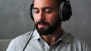 Cheerful bearded man putting off his headphones