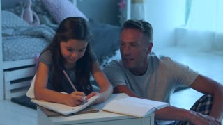 Cheerful caring father helping her daughter with her home work