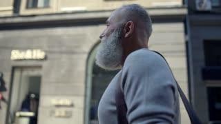 Cheerful elderly gentleman walking down street