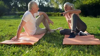 Cheerful elderly sporty couple sitting on the exercise mats
