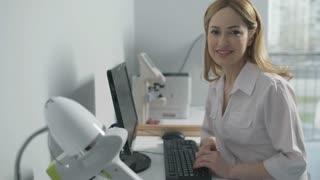 Cheerful medical professional sitting at computer