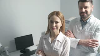 Cheerful medical specialists crossing arms while posing