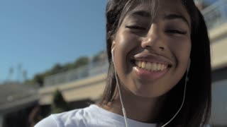 Close up of beaming girl with earphones outdoors