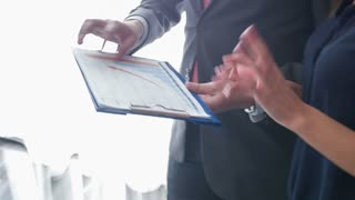 Close up of business executive showing diagram to colleague