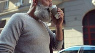 Close up of mature man drinking take away coffee