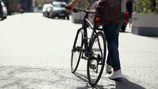Close up on adult man with bicycle promenading outdoors