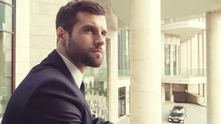 Confident businessman standing near office building