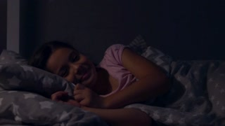 Cute cheerful little girl lying in her bed