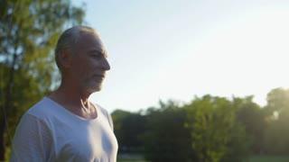 Delighetd aged man drinking water after running