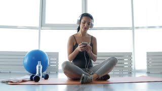 Delighted mood. Full length of positive young woman sitting on fitness mat while wearing earphones and listening to music