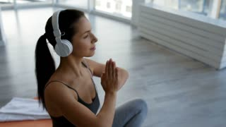Delightful mood. Close up of young cheerful woman looking at you with a pleasant smile while listening to music and doing yoga exercises