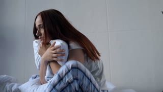 Depressed adult woman embracing her pillow