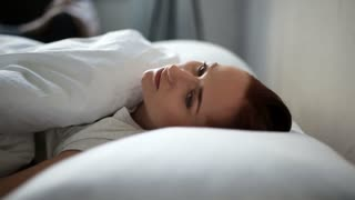 Depressed adult woman lying in bed