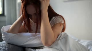 Depressed mature woman sitting in bed