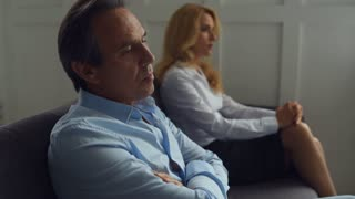 Disappointed couple sitting in psychologists office