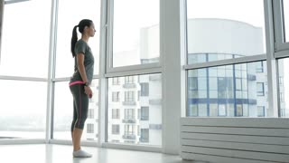 Doing exercises. Full length of pleasant young woman training in front of the window while having restful mood