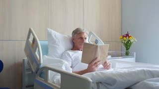 Dolly shot of a thoughtful aged man reading book in a hospital