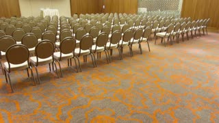 Dolly shot of conference hall with chairs in rows