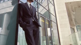 Dolly shot of positive businessman standing near office building