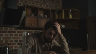 Drown in solitude. Close up of dispirited young man sitting at the table while drinking alcohol and propping his head up