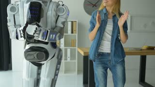 Excited girl dancing with robotic machine