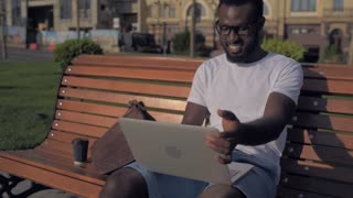 Excited man relaxing and beaming widely after working on laptop