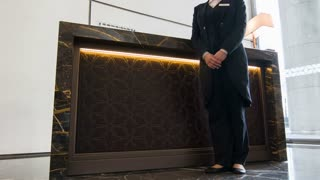 Female concierge standing near reception desk
