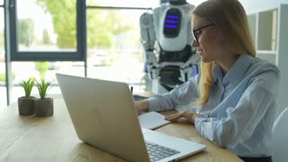 Female office worker talking to robot while typing