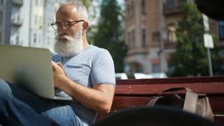 Focused bearded gentleman working outdoors