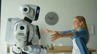 Friendly robot and young woman hugging each other
