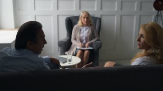 Frustrated couple having discussion with psychologist