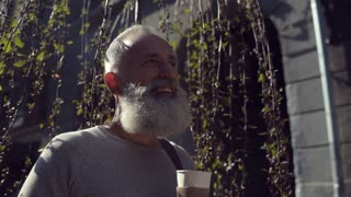 Handsome bearded man drinking delicious coffee outdoors