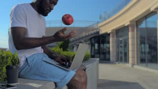Handsome young man with laptop throwing apple up