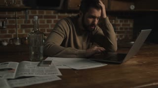 Hardships. Distressed young man sitting at the table and drinking alcohol while looking at payment bills and using a laptop