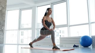 Healthy body. Full length of young sportive woman busy with doing exercises while listening to music and having endless energy for further training