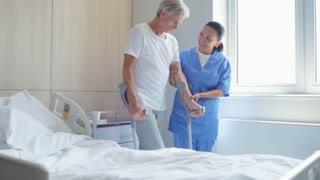 Helping nurse helping a senior man to walk on crutches