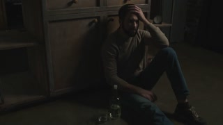 Hopeless. Young bearded man sitting on the floor while drinking alcohol and feeling depressed