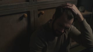 In despair. Close up of young bearded man sitting on the floor while drinking alcohol and expressing sadness
